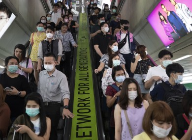 Commuters wear face masks to protect themselves from new virus at at skytrain station in Bangkok, Thailand.