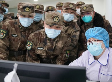 Members of a military medical team take over the work from a medical worker at Wuhan Jinyintan Hospital