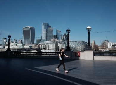 A woman walking along the Thames path near City Hall in London today.