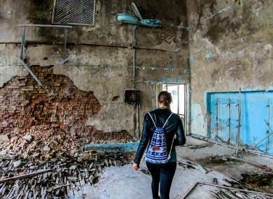 A woman walks in an abandoned school gym in Pripyat.