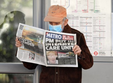 A man wearing a facemask at a bus stop reading a newspaper outside St Thomas' Hospital in Central London.