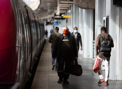 People wearing face masks wait for a train at Gare du Nord during the lockdown in Paris