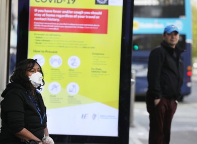 A woman wears a face mask as she waits for a bus in Dublin city.