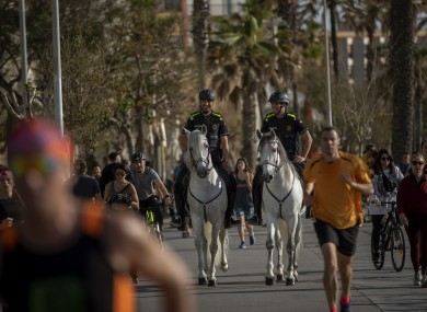 Mounted police patrol on horses as people exercise on a seafront promenade in Barcelona today.