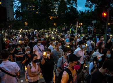 Protesters shine their phone lights while marching in commemoration of the first year anniversary