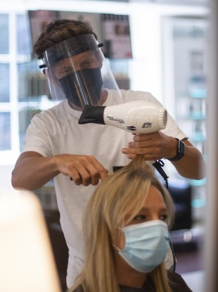 Senior Style Director Nick Peters wears PPE as he cuts a staff member's hair at Daniel Galvin hairdressers in Marylebone, England, in preparation for reopening.