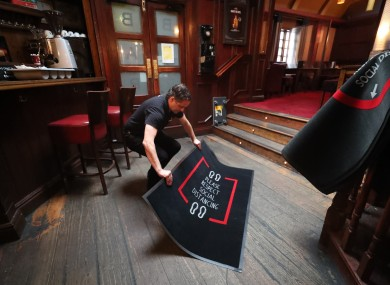 Mariusz Brzyk assistant manager of Paddy Cullens pub in Dublin lays out social distancing mats