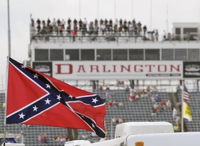In this Sept. 5, 2015, file photo, a Confederate flag flies in the infield before a NASCAR Xfinity auto race at Darlington Raceway.