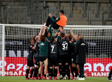Werder Bremen's Claudio Pizarro is thrown into the air by his teammates after the end of the game against Heidenheim.