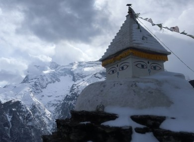 A Buddhist stupa in front of a mountain in the Nepali Himalayas