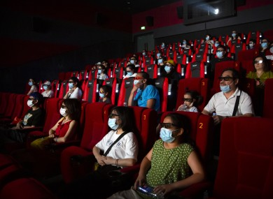 People wearing face masks to protect against the coronavirus watch the film