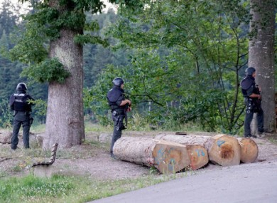 Police officers stay outside a wooded area on a road near Oppenau.