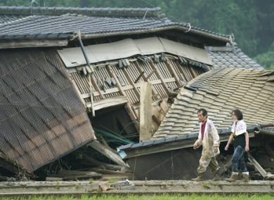 A couple walks in front of a damaged house in Kumamoto.