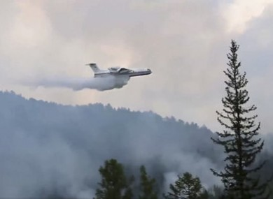An amphibious aircraft releasing water to extinguish a fire  in southern Siberia,