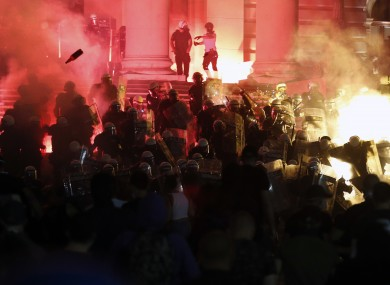 Protesters clash with riot police on the steps of the Serbian parliament in Belgrade last night.