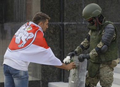 An opposition supporter presents a flower to soldier in Minsk yesterday