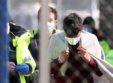 Border Force officers process men thought to be migrants after they were brought into Dover, Kent. 17 April.