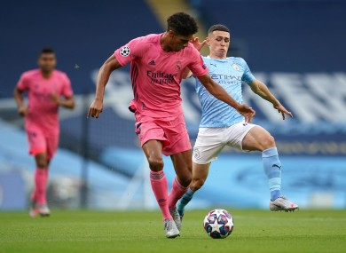 Real Madrid's Raphael Varane (left) and Manchester City's Phil Foden battle for the ball.