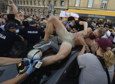 An activist climbs onto a police car while protesting in Warsaw.