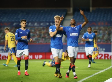 Joe Aribo celebrates, chased by team mate Filip Helander, after scoring to give Rangers a 3-0 lead last night.