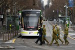 Victorian Police officers and ADF personnel are on Bourke street in Melbourne.