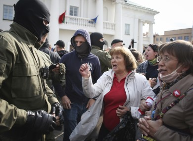 A woman shouts standing in front of police line during a protest in Minsk today.