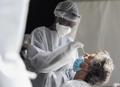 A nurse in Paris performing a PCR test.
