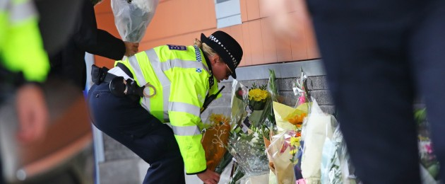 A police officer lays flowers outside Croydon Custody Centre in south London where a fellow police officer was shot dead today.