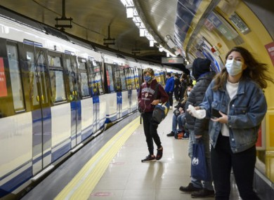 Passengers wearing face masks wait for the metro at the station in Madrid.