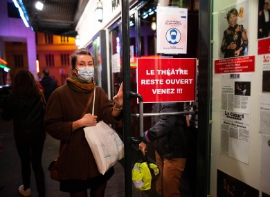 A spectator leaves the Theatre Montparnasse in Paris last night before the curfew comes into effect.