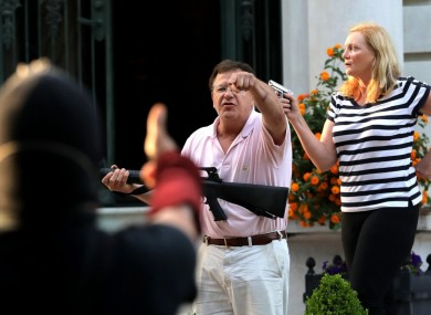 Armed homeowners Mark T. and Patricia N. McCloskey stand in front their house as they confront protesters marching to St. Louis Mayor Lyda Krewson's house on June 28, 2020.