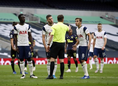 Tottenham Hotspur players surround referee Peter Bankes after he awards a penalty against them.