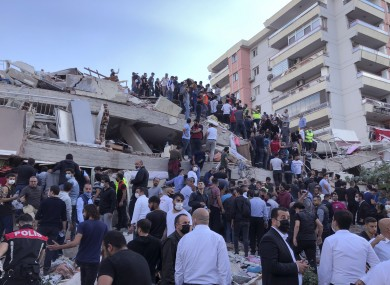 Rescue workers and local people try to reach residents trapped in the debris of a collapsed building in Izmir.