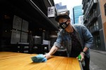 Patrick Walsh, staff member of Hochi Mama restaurant sanitises a table in preparation to reopen the restaurant in Melbourne.