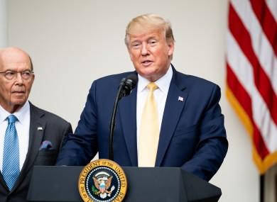 Secretary Ross (left) speaking alongside President Trump at a White House event last year
