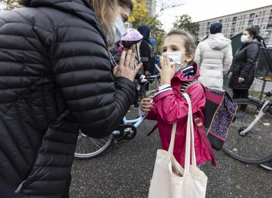 A mother and her daughter wave goodbye as school resumes with new sanitary precautions during the lockdown in Strasbourg, Eastern France which went into shutdown mode on Friday.