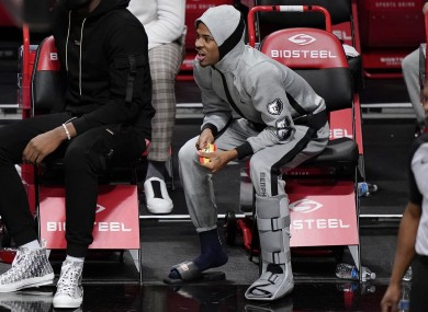 Memphis Grizzlies guard Ja Morant wearing a boot on his left leg after suffering an injury against Brooklyn Nets.