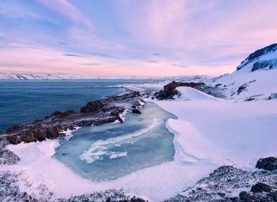 A small frozen lake and the Barents Sea coastline, Russia