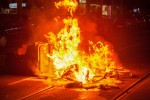 A rubbish container and bicycles are seen burning on the street in The Hague last night.
