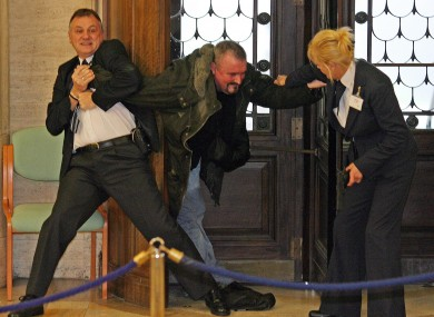 Michael Stone being restrained by security staff after forcing the suspension of the Stormont Assembly in 2006