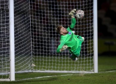 Jason Steele saves a penalty kick from Newport County's Josh Sheehan.