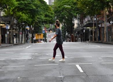 A woman crosses an empty Edward Street in Brisbane.