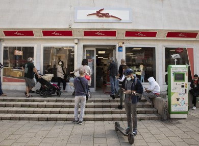 Israelis wait outside a post office in Tel Aviv as restrictions eased today