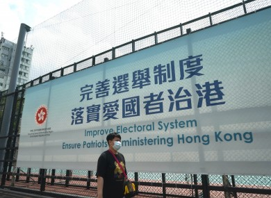 A man walks past a government advertisement to promote the new Hong Kong electoral system reform