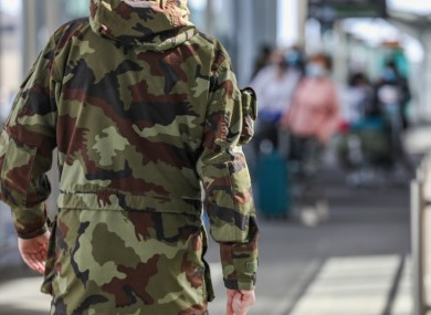 A member of the Defence Forces prepares to escort passengers to mandatory quarantine from Dublin Airport.