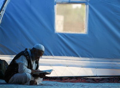 A man in a Syrian refugee camp reading.
