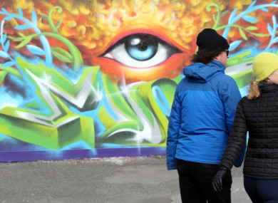 A man and a woman pictured passing by a mural at Grand Canal Dock Dublin on bank holiday Easter Monday