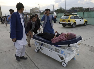 An injured school student is transported to a hospital after a bomb explosion in Kabul