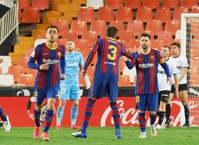 Lionel Messi, Gerard Pique and Sergino Dest celebrating a goal against Valencia.