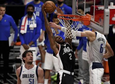 Los Angeles Clippers' Kawhi Leonard (2) slam-dunks over Dallas Mavericks' Kristaps Porzingis (6).